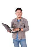 Uśmiechnięty Męski Azjatycki uczeń Pisać na maszynie na laptopie Zdjęcie Stock