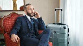 Uśmiechnięty męski biznesmen opowiada w eleganckim kostiumu mieć biznesu wywoławczego używa smartphone zbiory