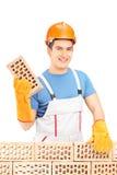 Uśmiechnięty męski budowniczy buduje ściana z cegieł Obraz Stock
