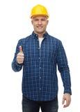 Uśmiechnięty męski budowniczy w hełmie pokazuje aprobaty Fotografia Royalty Free