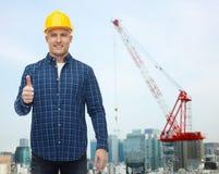 Uśmiechnięty męski budowniczy w hełmie pokazuje aprobaty Zdjęcia Stock