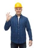 Uśmiechnięty męski budowniczy w hełmie pokazuje ok znaka Zdjęcia Stock