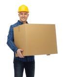 Uśmiechnięty męski budowniczy w hełmie z kartonem Obraz Stock