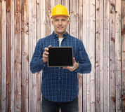 Uśmiechnięty męski budowniczy w hełmie z pastylka komputerem osobistym Obraz Stock