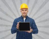 Uśmiechnięty męski budowniczy w hełmie z pastylka komputerem osobistym Zdjęcie Stock