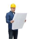 Uśmiechnięty męski budowniczy w hełmie z projektem Zdjęcia Stock