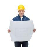 Uśmiechnięty męski budowniczy w hełmie z projektem Fotografia Royalty Free