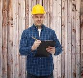 Uśmiechnięty męski budowniczy w hełmie z schowkiem Obraz Stock