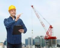 Uśmiechnięty męski budowniczy w hełmie z schowkiem Zdjęcia Royalty Free