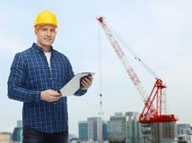 Uśmiechnięty męski budowniczy w hełmie z schowkiem Zdjęcie Stock
