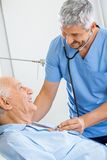 Uśmiechnięty Męski dozorca Egzamininuje Starszego mężczyzna zdjęcie stock