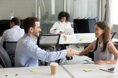 Uśmiechnięty męski i żeński kolegi handshaking dziękuje dla succ zdjęcie stock