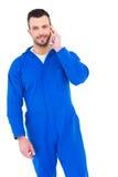 Uśmiechnięty męski mechanik używa jego telefon komórkowego Fotografia Royalty Free