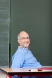 Uśmiechnięty męski nauczyciel relaksuje w sala lekcyjnej Fotografia Royalty Free