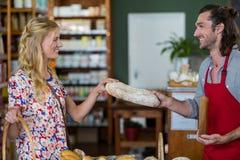 Uśmiechnięty męski personel daje bochenkowi chleb kobieta Zdjęcia Stock