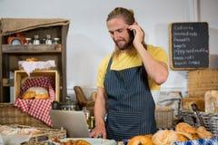 Uśmiechnięty męski personel opowiada na telefonie komórkowym podczas gdy pracujący na laptopie przy kontuarem Zdjęcie Stock