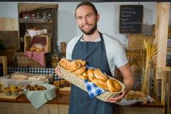 Uśmiechnięty męski personel trzyma łozinowego kosz różnorodni chleby przy kontuarem Obrazy Royalty Free