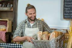 Uśmiechnięty męski personel trzyma kosz baguettes przy kontuarem Obrazy Stock