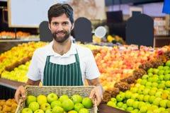 Uśmiechnięty męski personel trzyma kosz zielony jabłko przy supermarketem Fotografia Stock