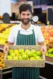 Uśmiechnięty męski personel trzyma kosz zielony jabłko przy supermarketem Zdjęcia Stock