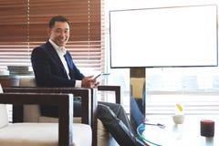 Uśmiechnięty męski pomyślny finansisty mienia dotyka ochraniacz podczas gdy siedzący pobliski pustego miejsca tv ekran z kopii pr Zdjęcie Stock