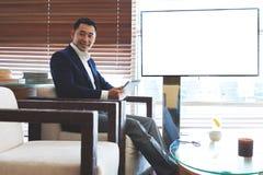 Uśmiechnięty męski pomyślny finansisty mienia dotyka ochraniacz podczas gdy siedzący pobliski pustego miejsca tv ekran z kopii pr Fotografia Stock