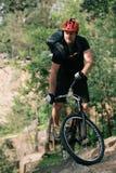 uśmiechnięty męski próbny rowerzysta w ochronnej hełm jazdie na halnym bicyklu obrazy stock