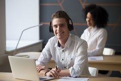 Uśmiechnięty męski pracownik w słuchawki pozuje dla obrazka obraz stock