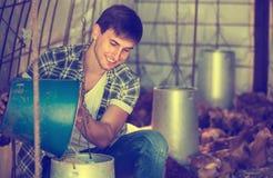 Uśmiechnięty męski rolnik daje żywieniowemu materiałowi Obraz Stock