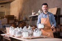 Uśmiechnięty męski rzeźbiarz ma ceramics w rękach Zdjęcia Stock