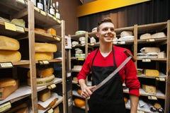 Uśmiechnięty męski sprzedawcy mienia nóż w serowym sklepie Fotografia Royalty Free