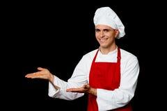 Uśmiechnięty męski szef kuchni przedstawia coś Obraz Stock