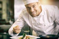Uśmiechnięty męski szefa kuchni garnirowania jedzenie w kuchni Zdjęcia Stock