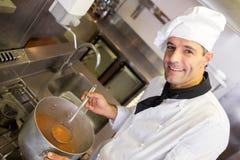 Uśmiechnięty męski szefa kuchni narządzania jedzenie w kuchni Fotografia Royalty Free