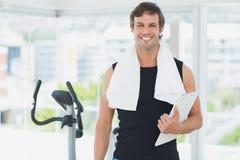 Uśmiechnięty męski trener z schowkiem w jaskrawym gym Zdjęcie Stock