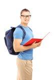 Uśmiechnięty męski uczeń czyta książkę z plecakiem Obraz Stock