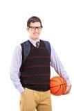 Uśmiechnięty męski uczeń trzyma koszykówkę z szkolną torbą Zdjęcie Stock