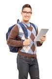 Uśmiechnięty męski uczeń trzyma pastylkę z plecakiem Obraz Stock
