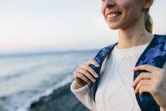 Uśmiechnięty młoda kobieta podróżnik w biel ubraniowej pozyci na brzeg i spojrzeniach przy morzem Obraz Stock