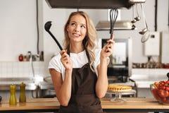 Uśmiechnięty młoda kobieta szefa kuchni kucharz w fartuchu obraz royalty free