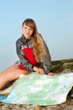 Uśmiechnięty młoda kobieta wycieczkowicza obsiadanie na wierzchołku góra Zdjęcie Stock