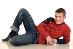 Uśmiechnięty młodego człowieka lying on the beach na podłoga fotografia stock