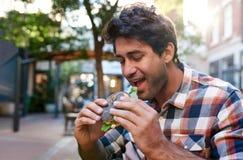 Uśmiechnięty młodego człowieka obsiadanie na zewnątrz jeść wyśmienicie bagel Zdjęcia Royalty Free