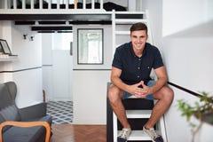 Uśmiechnięty młodego człowieka obsiadanie w jego nowożytnym loft mieszkaniu Zdjęcie Stock