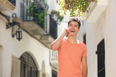 Uśmiechnięty młodego człowieka odprowadzenie w miasteczku z telefonem komórkowym Zdjęcia Royalty Free