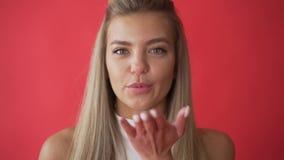 Uśmiechnięty młodej kobiety dosłania powietrza buziak kamera odizolowywająca nad czerwonym tłem zdjęcie wideo