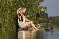 Uśmiechnięty młodej kobiety obsiadanie blisko wody Obraz Stock