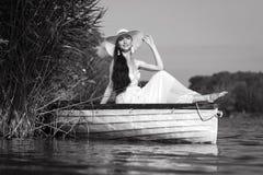 Uśmiechnięty młodej kobiety obsiadanie na łodzi w lecie Obrazy Royalty Free