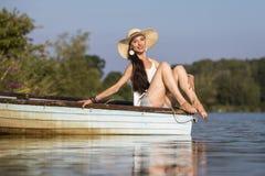 Uśmiechnięty młodej kobiety obsiadanie na łodzi w lecie Zdjęcia Royalty Free