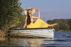 Uśmiechnięty młodej kobiety obsiadanie na łodzi w lecie Zdjęcie Royalty Free